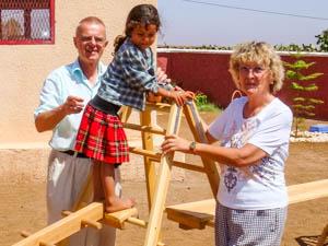 Helga und Jürgen Münstermann mit einem Kindergartenkind bei einer Übung auf der Außenanlage